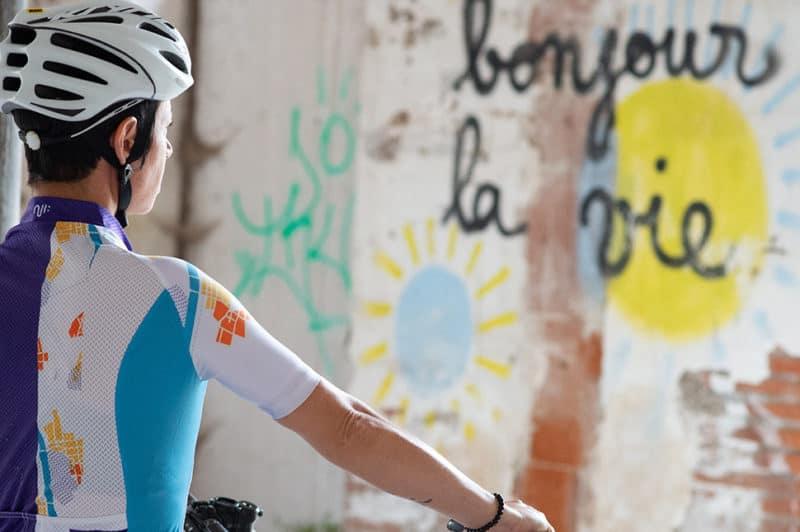 """Cycliste féminine devant un tag """"bonjour la vie"""""""